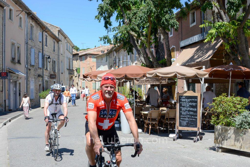 Cyclists pasing the Cafe de la Poste, Goult